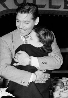"Clark Gable grabs Judy Garland in a bear hug after she sings ""(Dear Mr. Gable) You Made Me Love You"" at his birthday party in 1938."