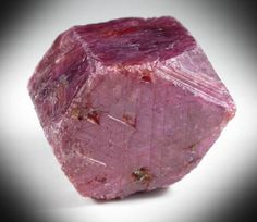 Well crystallized ruby crystal, with lustrous crystal faces that have complex crystallization patterns on the faces.