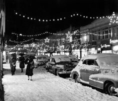 1940s 1950s WINTER CITY STREET SCENE WITH PEDESTRIANS IN SNOW CHRISTMAS LIGHTS Stock Photos