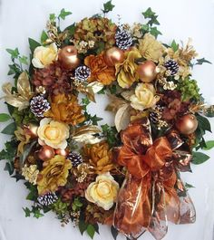 "The wreath is embellished with tan color Peonies, gold orange Roses, and light brown/green/olive green Hydrangeas. The wreath is accented with five sparkle Apples, one Pomegranate, and one Peach, and seven white tip Pine Cones. I finish the wreath with a gold/brown/orange Ribbon Bow.  The wreath measures from tip to tip at 27"" (L) x 27"" (W) x 7.5""(D)."