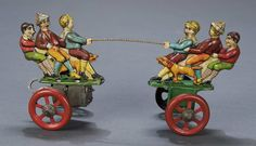 """8"""" German lithographed tin mechanical toy by Gebrüder Einfalt, early 20th century. Two sets of three boys are posed as if having a tug of war on two-wheeled carts attached by a spiral metal rod which also balances the carts. When wound, the carts move back and forth as though first one team is winning, and then the other."""