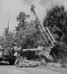 American GI examines a disabled FlaK 36 88mm German gun near the French town of Montbur on June 20, 1944. Before abandoning the gun, its crew used high explosive to destroy its barrel and render it unusable.