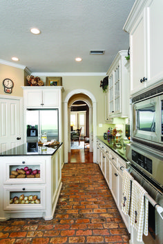Old brick floors and gleaming granite countertops make for a New Orleans-style kitchen. Description from cy-fairlifestylesandhomes.com. I searched for this on bing.com/images