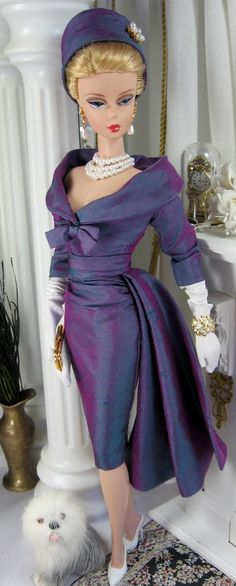The crown jewel of sheath dress with flattering fit, lush styling details and Mad Men vintage appeal. The dress is cut from a irridescent violet silk dupioni, fully lined, and features a wide collared decollete with front bow detail, three-quarter length sleeves, and ruched waist band. The skirt is gathered asymmetrical into a soft side drape and buttons over snaps closes the back. The matching bias cut hat is fully lined.  BROOCH IS FOR STYLING PURPOSES ONLY AND NOT INCLUDED.   SHOES, ...