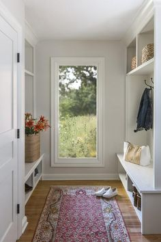 Chic mudroom features a tall picture window flanked by white quartz top benches with overhead shelves | R Cartwright Design