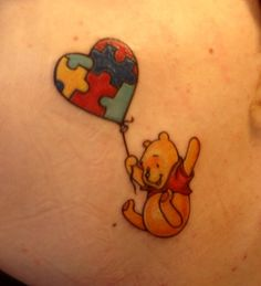 A super cute tattoo of Winnie the Pooh flying with the help of a puzzle patterned balloon