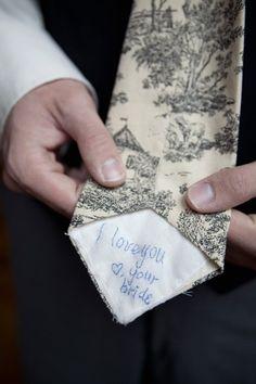 Bride writes on grooms tie
