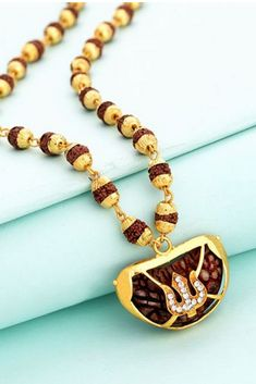 Trishul motif pendant threaded in a Rudraksha beads chain. Yellow gold plated and CZ gems embellished. Good for formal looks. Engraved Necklace, Beaded Necklace, Beaded Bracelets, Gold Necklace, Gold Jewelry, Jewelery, Chains For Men, Silver Pendants, Necklace Designs