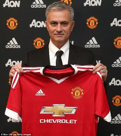 Jose Mourinho poses with a Manchester United shirt after being confirmed as the club's new manager