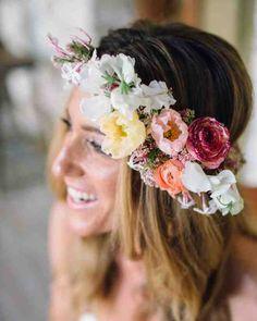 The bride wore a wreath of jasmine, sweet pea, Icelandic poppies, ranunculus, and rice flowers.