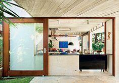 A bancada da cozinha fica exposta na área de circulação quando a porta de correr, feita de madeira e vidro, está aberta. A estrutura de concreto com vigas invertidas permite fixar os caixilhos diretamente na laje