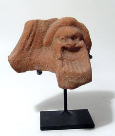 Theatre mask, Greek Silenus, 3rd-1st century B.C. reek terracotta pot support with a theatre mask of Papposeilenos with a long striated beard, within an arched panel, the back is plain, the edge of the fire bowl still evident, 11.6 cm high. Private collection