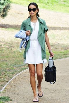 Jamie Chung wears a green jacket with a white dress, sandals, black bucket bag, and black sunglasses