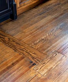 If you have vintage wood floors, patch the flaws. This patch is where the wall for a pantry was removed. It's part of the house history, not a flaw in the floor.