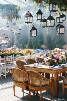 Mesa comunitária com decoração colorida para casamento na praia. Luminárias de latão e cadeiras de palha dão um charme especial. Foto: Duo Borgatto
