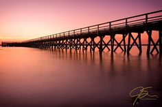 De basis van lijnen. LIjnenspel binnen een foto.   Leading into the distance, the pier at Ft. Foster in Kittery, Maine leads out over the milky smooth flow of the tide. The sky a pastel orange-pink as the sun sets