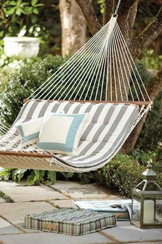hamac confortable, coussins de sol carrés et rayés et lanterne métallique dans le jardin