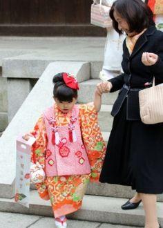 Crianças usam quimono em rito de passagem no Japão. Mãe ajuda filha a descer escada do santuário Meiji, em Tóquio, no Japão, durante celebração do festival Shichi-Go-San.  Fotografia: Yoshikazu Tsuno/AFP.