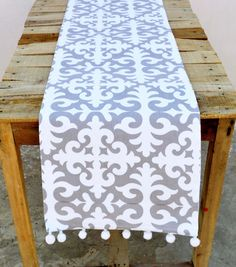 A gray on white print table runner with white pompom lace on 2 shorter sides. The design or pattern is inspired by classic Shyrdak felt rugs simplified