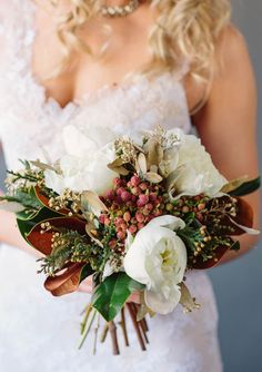 Magnolia wedding bouquet.  DIY:  - 10-12 large magnolia leaves with longer stems - 5 white/cream peonies - 5 stems of red brunia - 7 stems of gold spray-painted seeded eucalyptus - 5-7 stems of cedar or other evergreen
