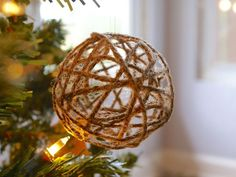 Wrap twine around a blown-up balloon and set the shape in place using Mod Podge. Remove the balloon after your project dries to create a glittery Christmas ornament for your lights to shine through.  Get the tutorial at Thinking Closet.