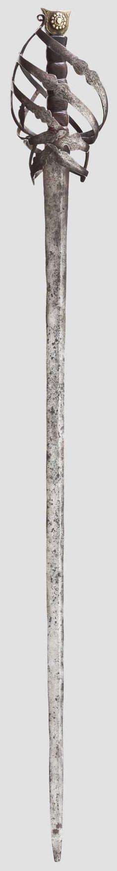 Schlanke, zweischneidige Klinge mit ungewöhnlichem asymmetrischen Mittelgrat. Typisches Korbgefäß mit geschnittenen Spangen mit Resten einer Gravur, Parierstange abgebrochen. Später belederte Hilze und flacher Katzenkopfknauf aus Messing. Metalloberflächen fleckig, patiniert und stellenweise narbig. Länge 106 cm.