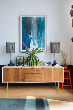 Gorgeous living room vignette with walnut and white midcentury credenza with tapered brass peg legs, wire cage table lamps, bright orange stool and beautiful framed turquoise print.