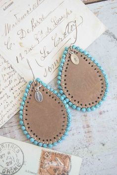 145.00 Large saddle brown leather drop shaped earrings with turquoise beads around the edges.
