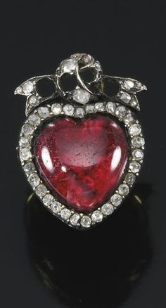 Garnet and diamond ring, 19th century composite the bezel set with a heart-shaped foil backed garnet framed with circular-cut diamonds to a similarly set bow surmount, size M, six diamonds deficient.