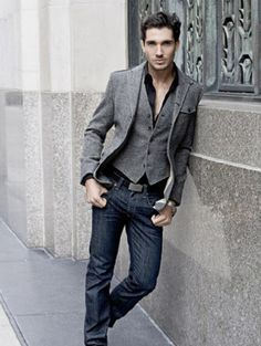 Open black shirt under a textured grey vest and jacket. / Amazingly he makes this outfit feel so laid-back.