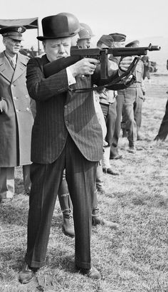 Winston Churchill squints as he test fires an American M1928 Thompson submachine gun, many of which were supplied to England under the Lend-Lease program. Note the unusual hybrid forestock with both descending pistol and horizontal hand grips ~