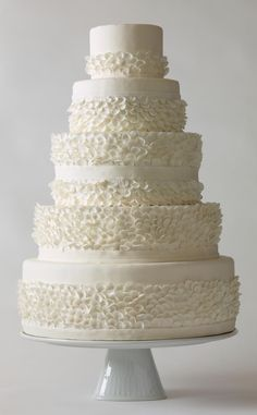 This simple, all-white wedding cake design is full of frilly texture. Each layer has its own smattering of three-dimensional petals, giving the cake a fanciful look and feel.