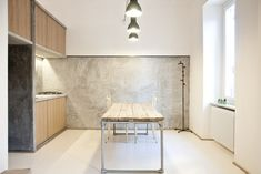 """""""It was supposed to be as naked as possible,"""" says Alexandru Popescu, one of the members of R3Architetti who helped design and build the 3 Vaults apartment. """"The furniture is absolutely included in the architecture;it's more like an indoor landscape instead of a typical open plan."""" The kitchen exemplifies their approach, with textured concrete walls contrasting with wood panels and salvaged industrial lighting. The table, custom built by R3Architetti, is made in part from pipes procured…"""
