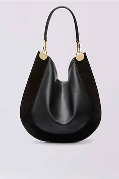 This modern hobo bag is made in a soft leather and suede, and accented with sleek gold hardware. It has a leather handle and zip closure.