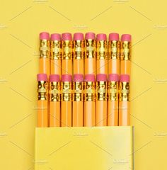 #New Pencils in Box  Closeup of a box of new pencils on a yellow background.