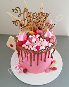Pink and chocolate Lolly Drip Cake with layers of White Velvet Cake and Whipped White Choc Ganache, topped with chocolate bark, meringue kisses, chocolates, lollies and sprinkles. Topper by Breakthrough CAD Design
