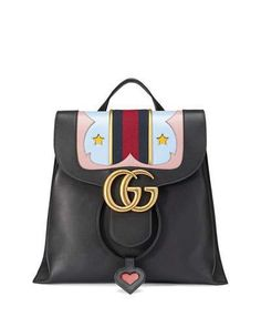"""Gucci GG Marmont Leather Backpack, Black - Gucci grained leather backpack with antiqued golden hardware. Western leather details with blue/red/blue web detail. Flat top handle, 1.5"""" drop. Adjustable chain shoulder straps. Flap with interlocking GG; magnetic closure. Drawstring top with heart pull. Interior, three slip pockets. 10.5""""H x 11.5""""W x 5.5""""D. """"GG Marmont"""" is made in Italy."""