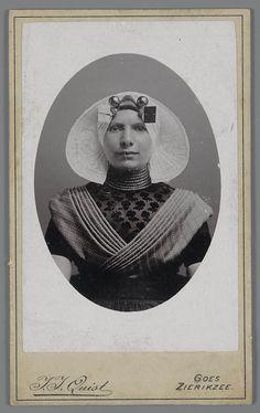 Vrouw in protestantse Zuid-Bevelandse streekdracht. Ze is gekleed in de zondagse dracht. Onder de kanten muts draagt ze een ondermuts met een oorijzer. Boven de gouden 'stikken' (de vierkante oorijzeruiteinden) zijn twee paar mutsenspelden in de ondermuts gestoken. De kanten muts is verstevigd met 'karkas', gemaakt van koperdraad, omwikkeld met blauw garen. Om haar hals draagt de vrouw een halssnoer met zeven strengen kralen, met een sluiting in de nek. #Zeeland #ZuidBeveland #protestant