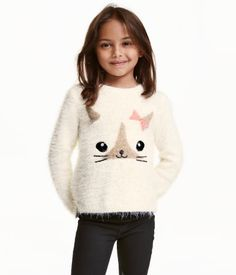 Knitted jumper in soft, eyelash yarn with a shimmering motif and short slits in the sides. Slightly longer at the back.