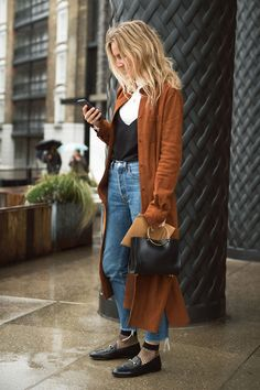 Brown Trench Coat + Black Cami over White T-Shirt + High-Waisted Jeans + Fishnet Socks with Black Loafers + Metal Bag // Street Style, Fashion Trends, Fashion Week, Women's Fashion