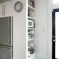 Extended Viewing  A false wall behind pantry cabinets nudges the units forward, making a freestanding refrigerator look like an expensive built-in. Beside the fridge, built-in shelves provide easily accessible storage in an almost-hidden niche.