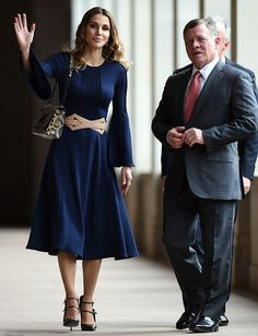 Queen Rania of Jordan donning a flowing navy blue dress complete with a tan belt, stepped out alongside her husband King Abdullah II of Jordan during their visit to the Australian War Memorial in Canberra on November 23, 2016.