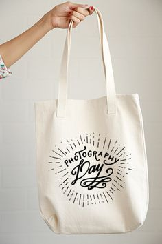 """Heading for a session? Start your big day with the right tote bag, the """"Photography Day"""" hand drawing tote. - 12.0 oz., 100% cotton canvas - 22"""" handles - Reinforced bottom - The design is printed usi"""