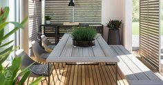 Besonders einladend ist die offene, überdachte Terrasse. Mit der Outdoorküche der Firma Röshults lassen sich warme Sommerabende genießen - Baufritz Musterhaus NaturDesign in Köln/Frechen