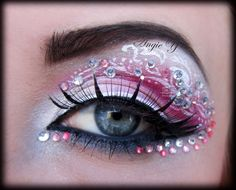 Pink and clear jewels accent artistic pink and white eye shadow with white scrolls.
