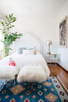 A feathery fishtail palm nestles near an all-white bed in a bohemian bedroom.