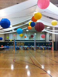 Trying to transform a gigantic gym into a fun, colorful dance hall didn't cost much!  $200 on paper lanterns, a couple of rolls of plastic table cloths, some white christmas lights, chair ties and some imagination is all it took.