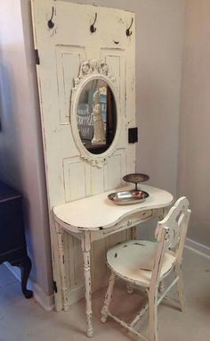 Vintage side table attached to a salvaged door with hooks and a mirror added. Love that they kept the hardware on the door. Shabby chic perfection!