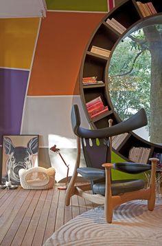 Circle window framed bookshelf: amazing. Plus, love the wall colors/patterning.