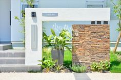 〈Natural Flavor 門柱・門塀〉 『住宅のコンセプトを継承する庭』 表札、インターホン、ポストをスマートに組み込んだ門柱。錆色の自然石が景色に温もりを与えます。  田主丸緑地